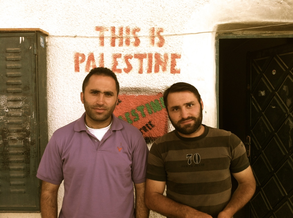 Brothers Issa and Ahmed Amro, nonviolent activists and organizers, stand outside of their community center in occupied Hebron.