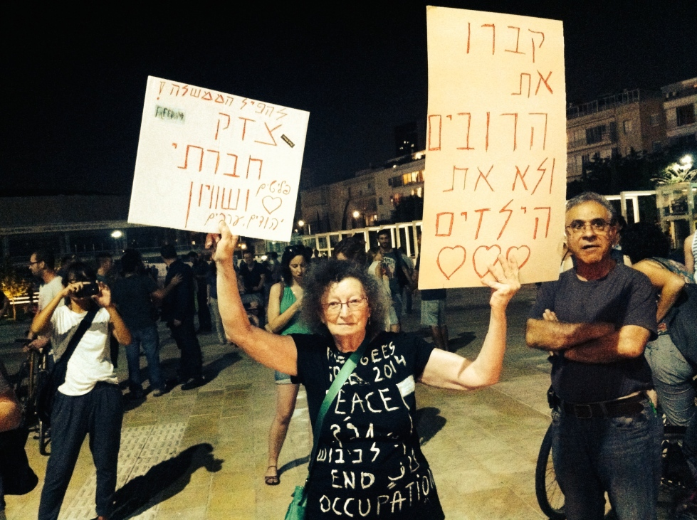 "A woman who I recognized from Women in Black stands at a demonstration with two signs that read: ""Bury the rifles and not the children"" and ""Topple the government! Social justice and equality. Refugees Jews and Arabs."""
