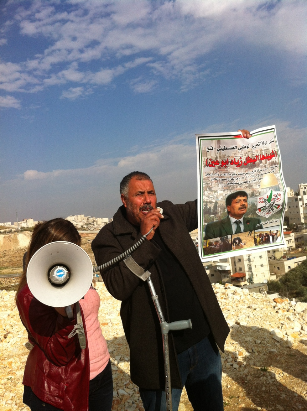 Activist Mohammad Abu Hummus holding up a poster of Ziad Abu Ein. Issawiya, East Jerusalem