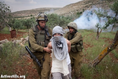 File photo of Israeli soldiers arresting a masked settler youth. (Photo: Oren Ziv/Activestills.org)